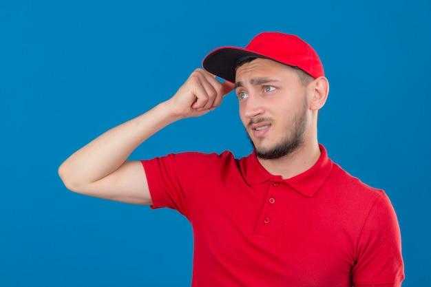 Jonge bezorger met rood poloshirt en pet verward voelt zich twijfelachtig en onzeker over geïsoleerde blauwe achtergrond