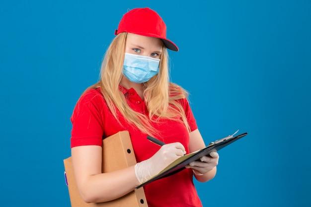 Jonge bezorgvrouw die rode poloshirt en pet in medisch beschermend masker draagt ?? die zich met pizzadoos en klembord schrijven op zoek zelfverzekerd over geïsoleerde blauwe achtergrond
