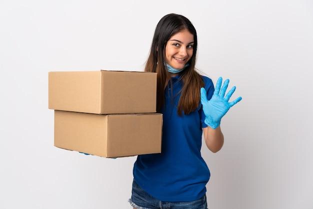 Jonge bezorgvrouw die tegen het coronavirus beschermt met een masker dat op witte muur wordt geïsoleerd die met hand met gelukkige uitdrukking groet