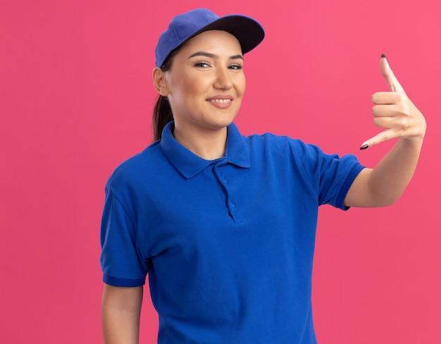 Jonge bezorgvrouw in blauw uniform en pet die naar de voorkant kijkt die vrolijk lacht en bel me gebaar maakt dat zich over roze muur bevindt