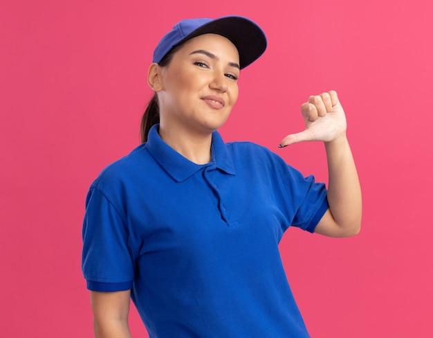 Jonge bezorgvrouw in blauw uniform en pet gelukkig en zelfverzekerd wijzend met de duim naar zichzelf staande over roze muur
