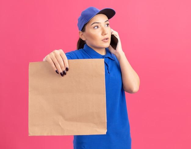 Jonge bezorgvrouw in blauw uniform en pet met papieren pakket die verward kijkt terwijl ze over een mobiele telefoon praat die over de roze muur staat