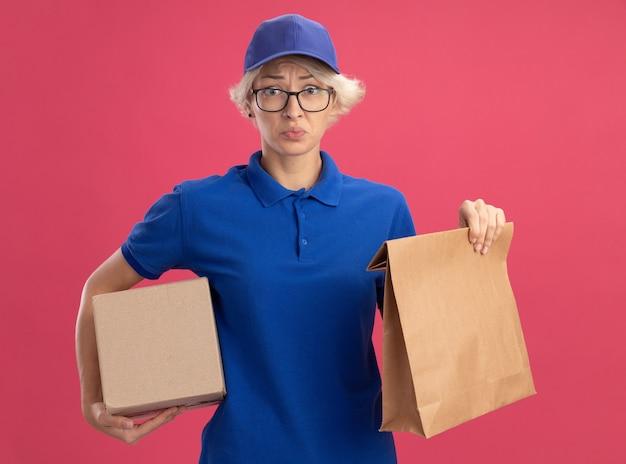 Jonge bezorgvrouw in blauw uniform en pet met papieren pakket en kartonnen doos met droevige uitdrukking op gezicht over roze muur
