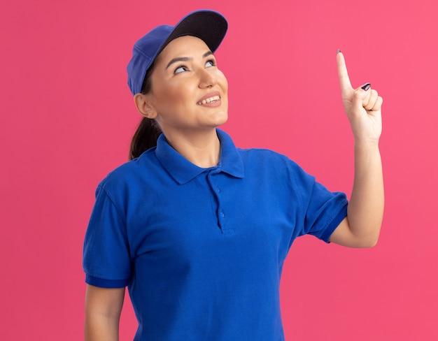 Jonge bezorgvrouw in blauw uniform en pet opzoeken met glimlach op gezicht wijzend met wijsvinger naar iets staande over roze muur