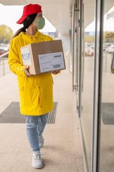 Jonge bezorgvrouw in gezichtsmasker en geel jasje die met pakket naar ingang loopt tijdens coronaviruspandemie