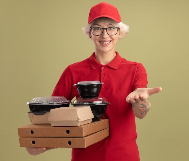 Jonge bezorgvrouw in rood uniform en pet die glazen draagt die pizzadozen en voedselpakketten houden die handen glimlachen die vriendschappelijk status over groene muur aanbieden
