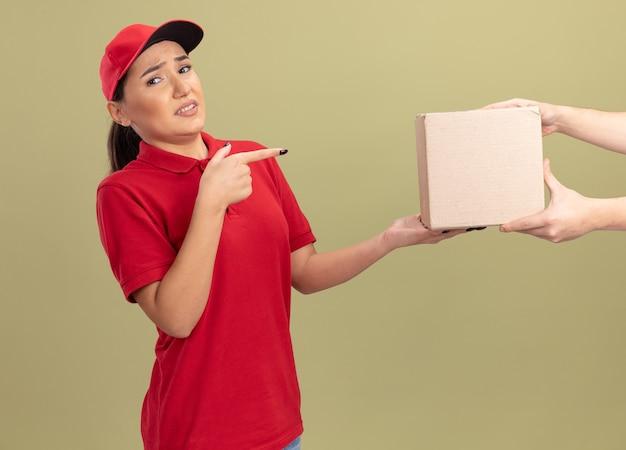 Jonge bezorgvrouw in rood uniform en pet die zich verward voelen terwijl ze het doospakket ontvangt dat met wijsvinger wijst naar de doos die zich over de groene muur bevindt