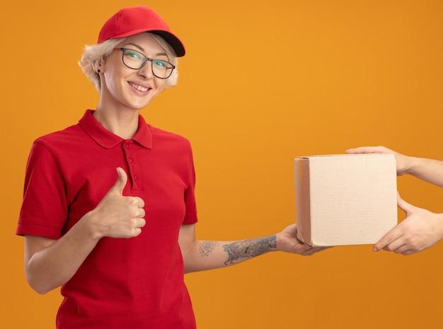 Jonge bezorgvrouw in rood uniform en pet glimlachend vriendelijke showin duimen omhoog terwijl het ontvangen van box-pakket staande over oranje muur