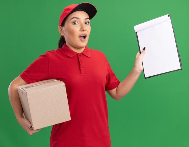Jonge bezorgvrouw in rood uniform en pet met kartonnen doos en klembord met blanco pagina's kijken naar voorzijde verbaasd staande over groene muur