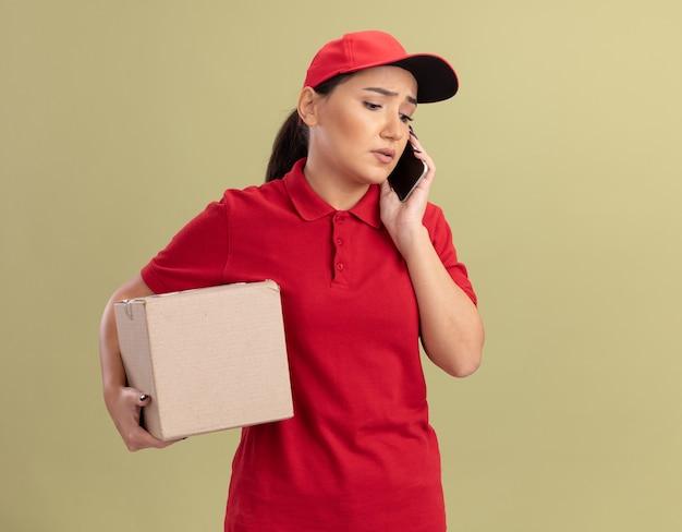 Jonge bezorgvrouw in rood uniform en pet met kartonnen doos op zoek verward tijdens het praten over de mobiele telefoon die zich over de groene muur bevindt