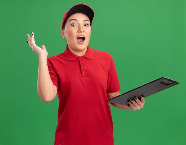 Jonge bezorgvrouw in rood uniform en pet met klembord kijkend naar voorkant verbaasd en verrast staande over groene muur