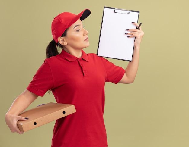 Jonge bezorgvrouw in rood uniform en pet met pizzadoos die klembord met balnk pagina's toont die zelfverzekerd over groene muur kijken