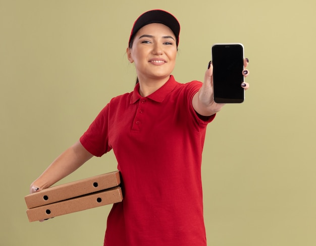 Jonge bezorgvrouw in rood uniform en pet met pizzadozen die mobiele telefoon tonen die voorzijde glimlachend vrolijk status over groene muur bekijken bekijken