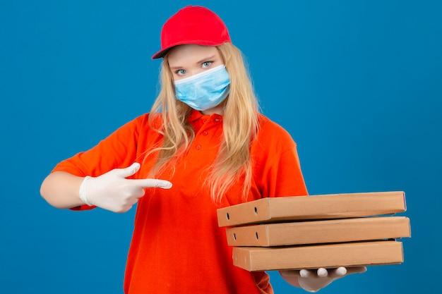 Jonge bezorgvrouw met oranje poloshirt en rode pet in medisch beschermend masker wijzend naar een stapel pizzadozen in de andere hand kijkt zelfverzekerd over geïsoleerde blauwe achtergrond