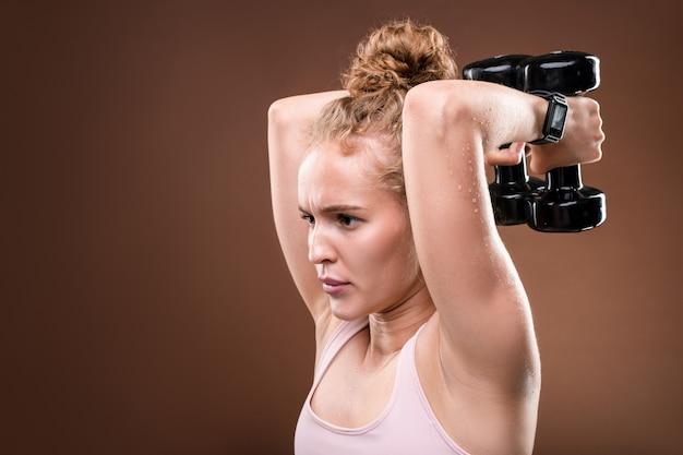 Jonge bezwete sportvrouw in activewear inspanning terwijl het doen van moeilijke oefening voor armspieren met halters