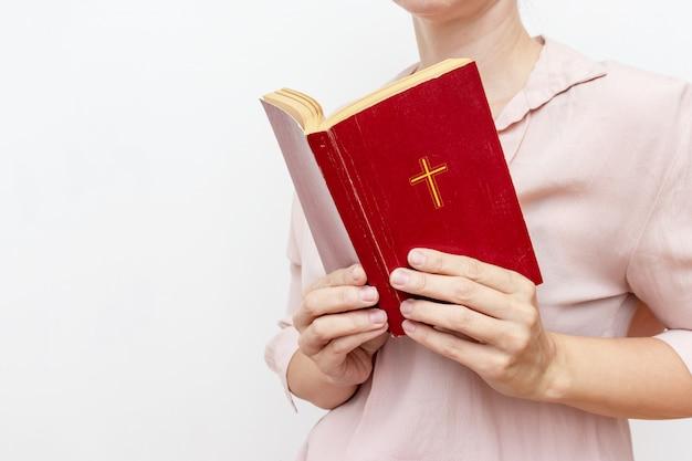 Jonge biddende christelijke vrouw die heilige bijbel met een kruis houdt