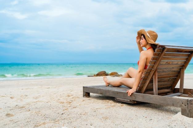 Jonge bikini vrouw zittend op een ligstoel in het zee strand op koh munnork island, rayong, thailand