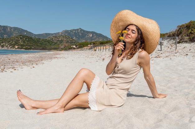 Jonge blanke aantrekkelijke vrouw zittend op het strand gele bloemen te houden en te ruiken. vrouw draagt jurk en strohoed.