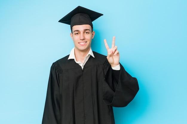 Jonge blanke afgestudeerd man met nummer twee met vingers.