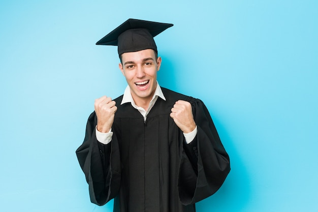 Jonge blanke afgestudeerde man juichen zorgeloos en opgewonden.