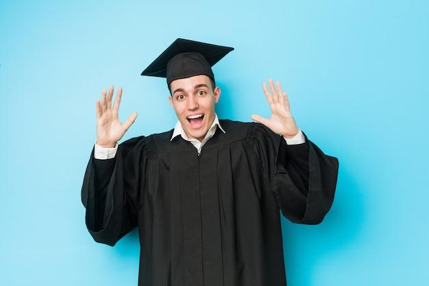 Jonge blanke afgestudeerde man viert een overwinning of een succes