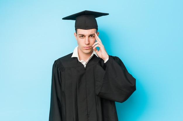Jonge blanke afgestudeerde man wijst zijn tempel met vinger, denken, gericht op een taak.