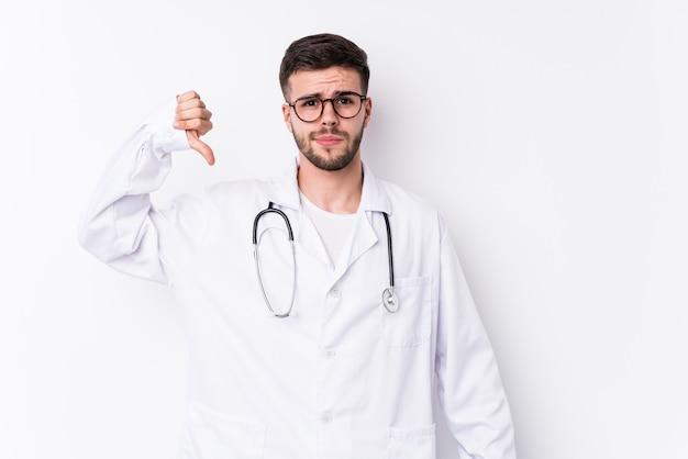 Jonge blanke arts man geïsoleerd met een afkeer gebaar, duimen naar beneden. meningsverschil concept.