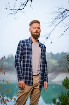 Jonge blanke bebaarde man in geruit hemd die alleen reist in het herfstbos en naar de zijkant kijkt...