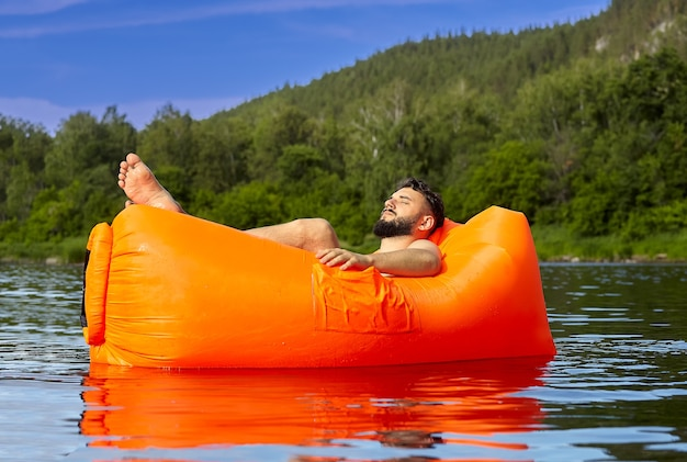 Jonge blanke bebaarde man is ontspannen op de oranje luchtbank, die op de rivier naast bos, eco-toerisme zwemt.