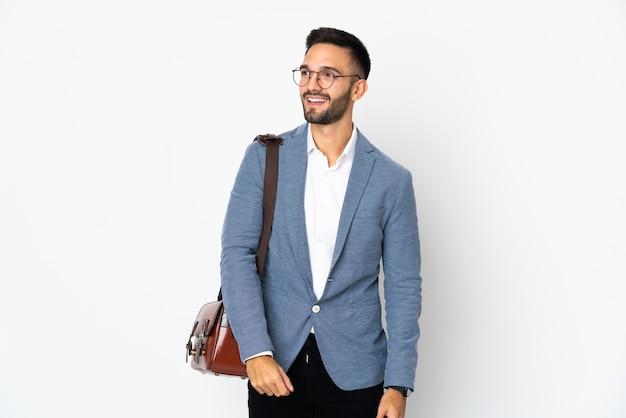 Jonge blanke bedrijfsmens die op witte muur wordt geïsoleerd die aan de kant kijkt en glimlacht
