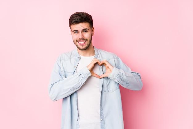 Jonge blanke bedrijfsmens die zich voordeed op wit geïsoleerd glimlachend en een hartvorm met handen tonen. <mixto>