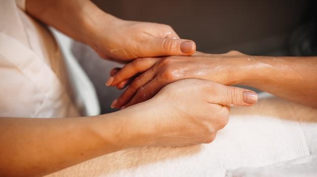 Jonge blanke beoefenaar masseert de hand van de cliënt met een natuurlijke lotion tijdens een spa-procedure