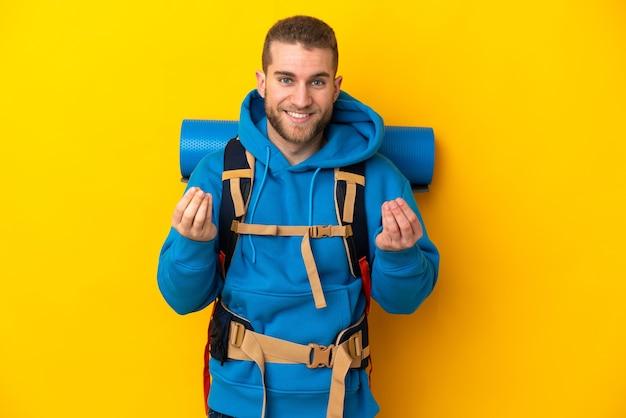 Jonge blanke bergbeklimmer man met een grote rugzak geïsoleerd op geel geld gebaar maken