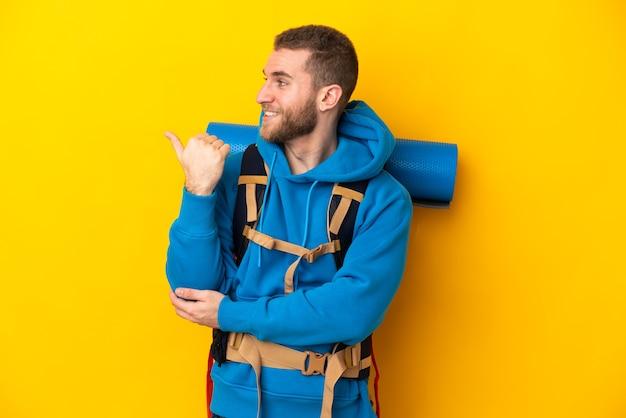 Jonge blanke bergbeklimmer met een grote rugzak geïsoleerd op een gele achtergrond die naar de zijkant wijst om een product te presenteren