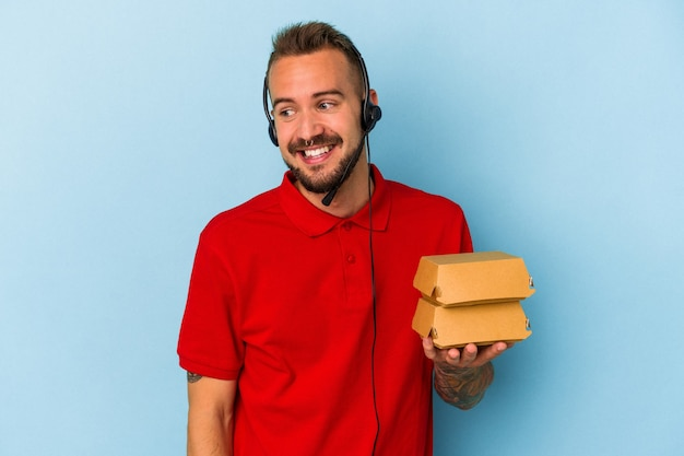 Jonge blanke bezorger met tatoeages met hamburgers geïsoleerd op een blauwe achtergrond kijkt glimlachend, vrolijk en aangenaam opzij.