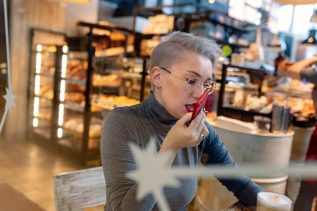 Jonge blanke blonde vrouw die audiobericht opneemt met smartphone die in café zit