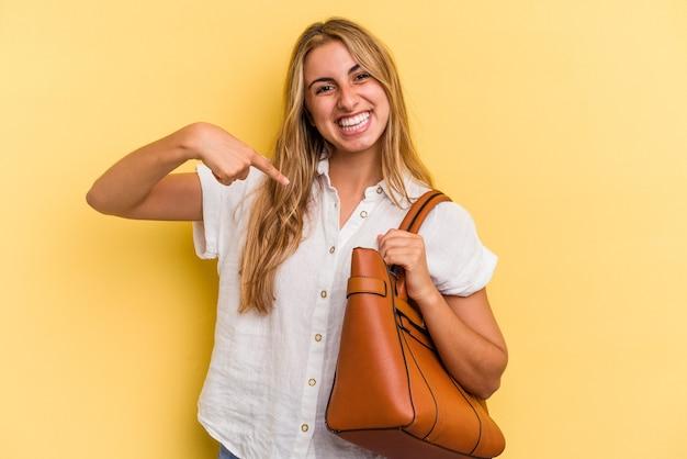 Jonge blanke blonde vrouw draagt een leren tas geïsoleerd op een gele achtergrond persoon die met de hand wijst naar een shirt kopieerruimte, trots en zelfverzekerd