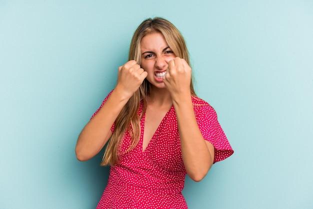 Jonge blanke blonde vrouw geïsoleerd op blauwe achtergrond boos schreeuwen met gespannen handen.