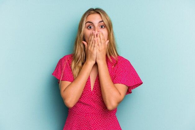 Jonge blanke blonde vrouw geïsoleerd op blauwe achtergrond geschokt die betrekking hebben op mond met handen.