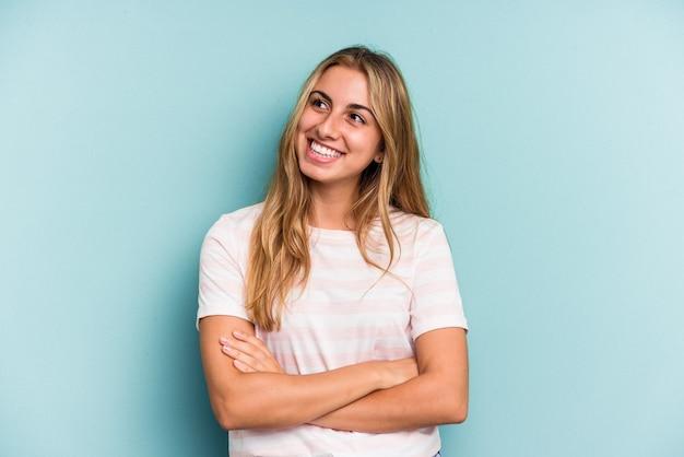 Jonge blanke blonde vrouw geïsoleerd op blauwe achtergrond glimlachend zelfverzekerd met gekruiste armen.