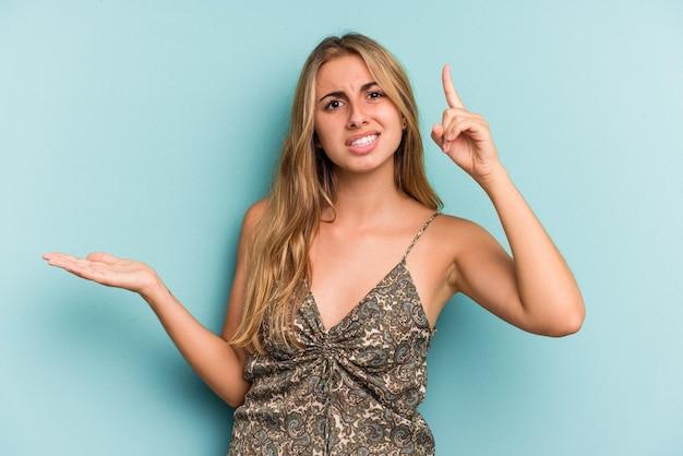 Jonge blanke blonde vrouw geïsoleerd op blauwe achtergrond houden en tonen van een product bij de hand.