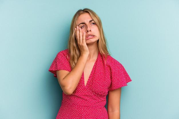 Jonge blanke blonde vrouw geïsoleerd op blauwe achtergrond moe en erg slaperig hand op het hoofd houden.