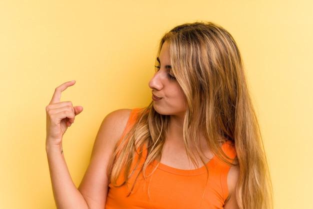 Jonge blanke blonde vrouw geïsoleerd op een gele achtergrond die met de vinger naar je wijst alsof uitnodigend dichterbij komt.