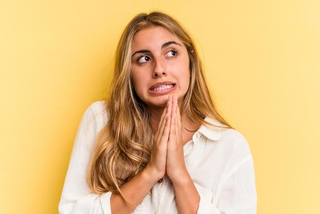 Jonge blanke blonde vrouw geïsoleerd op gele achtergrond bidden, toewijding tonen, religieuze persoon op zoek naar goddelijke inspiratie.