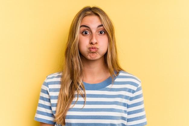 Jonge blanke blonde vrouw geïsoleerd op gele achtergrond blaast wangen, heeft een vermoeide uitdrukking. gezichtsuitdrukking concept. Premium Foto