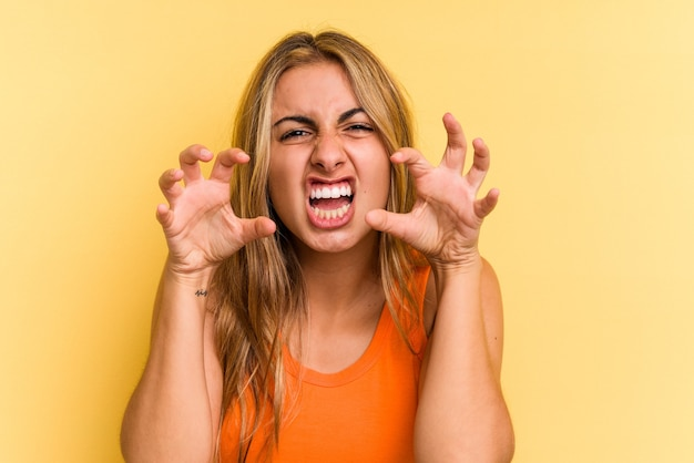 Jonge blanke blonde vrouw geïsoleerd op gele achtergrond boos schreeuwen met gespannen handen.