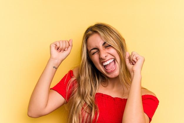 Jonge blanke blonde vrouw geïsoleerd op gele achtergrond dansen en plezier maken.