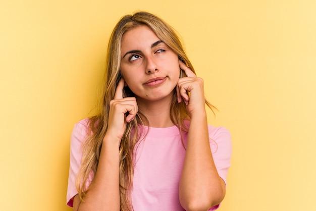 Jonge blanke blonde vrouw geïsoleerd op gele achtergrond die oren bedekt met vingers, gestrest en wanhopig door een luid ambient.