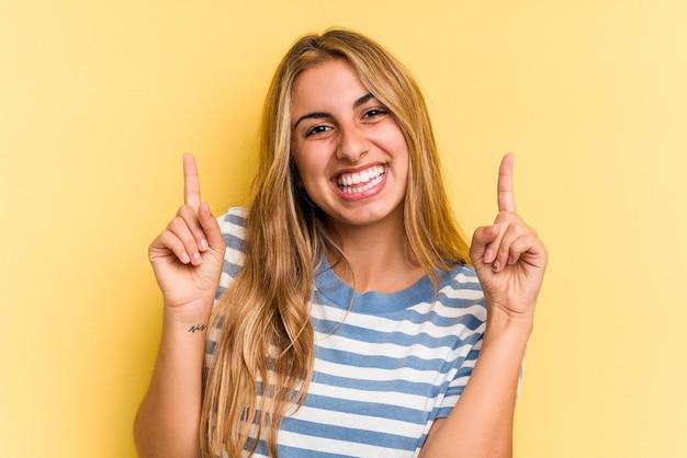 Jonge blanke blonde vrouw geïsoleerd op gele achtergrond geeft aan dat met beide voorvingers een lege ruimte wordt weergegeven.