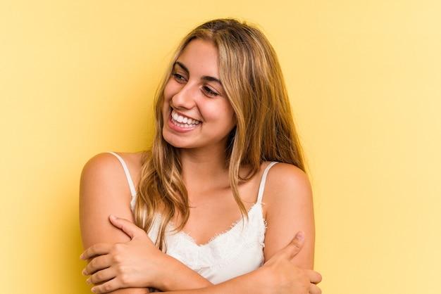 Jonge blanke blonde vrouw geïsoleerd op gele achtergrond glimlachend zelfverzekerd met gekruiste armen.